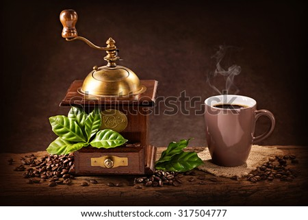 Coffee mill with beans and green leaves and a cup of coffee - stock photo