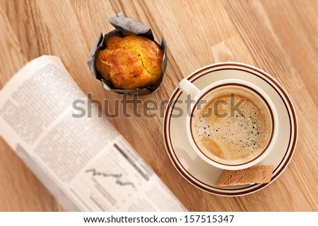 Coffee, muffin and rolled buisiness newspaper - stock photo