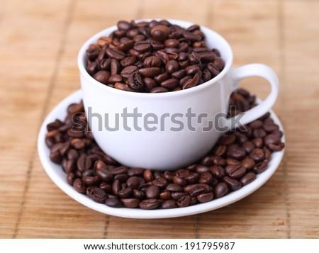 Coffee mug full of coffee beans - stock photo