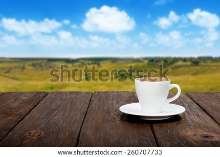 Coffee on wooden table with beautiful summer field background - stock photo
