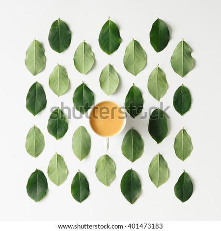 Coffee or tea on green leaves pattern on white background. Flat lay. - stock photo