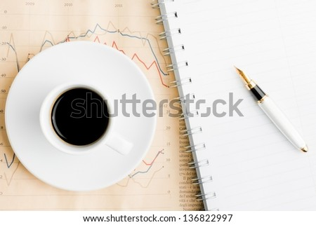 coffee over financial newspaper near notepad - stock photo