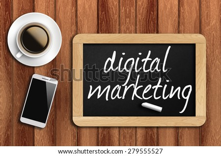 coffee, phone and chalkboard with digital marketing words. - stock photo