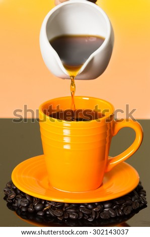 Coffee pouring from white glass kettle into colorful orange mug sitting on top of coffee beans and shiny surface. - stock photo