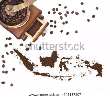 Coffee powder in the shape of Indonesia and a decorative coffee mill.(series) - stock photo