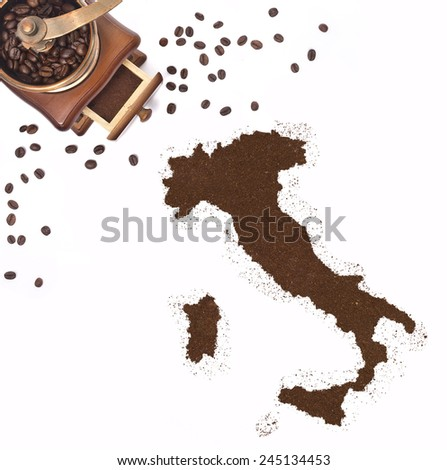 Coffee powder in the shape of Italy and a decorative coffee mill.(series) - stock photo