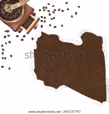 Coffee powder in the shape of Libya and a decorative coffee mill.(series) - stock photo