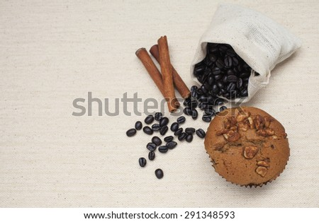 Coffee raisin muffin with coffee beans and cinnamon on canvas texture background top view - stock photo