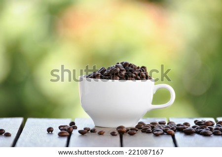 Coffee seeds with white cup and nice bokeh blur background. - stock photo