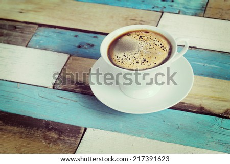 coffee served in a white cup on wooden table - stock photo