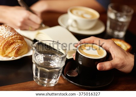 Coffee shop table with hands, espresso and someone writing - stock photo