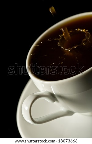 coffee splashing into white cup over black background - stock photo