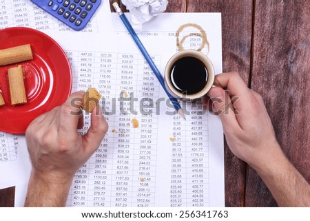 Coffee spots on the paper. Untidy workplace of accountant. Table numbers. Report, debit credit, verification digits. Calculator, wafers, chips, cup of coffee, man's hands and documents. - stock photo