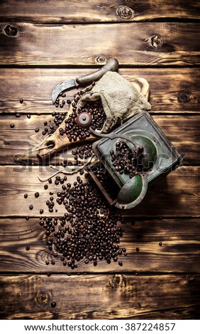 Coffee style. Old coffee grinder with fresh coffee . On wooden background. - stock photo