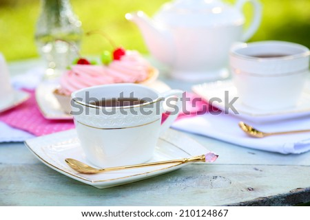Coffee table with teacups and tasty cakes in garden - stock photo