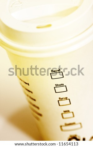 Coffee Take-out tumbler mood shot - intentional color-toning and selective focus on the word decaf - stock photo