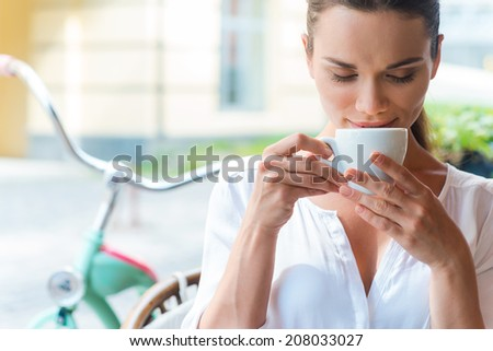 Coffee time. Attractive young woman drinking coffee and keeping eyes closed while sitting at the sidewalk cafe  - stock photo