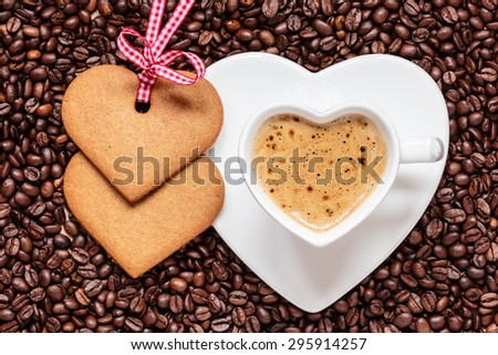 Coffee time concept. Heart shaped cup with cappuccino mocha and cookies gingerbread on coffee beans background. Top view - stock photo