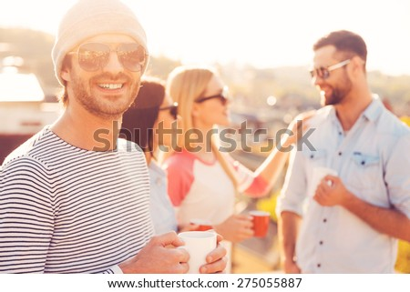 Coffee time. Handsome young man in hat holding coffee cup and smiling while standing near his friends on the roof terrace - stock photo