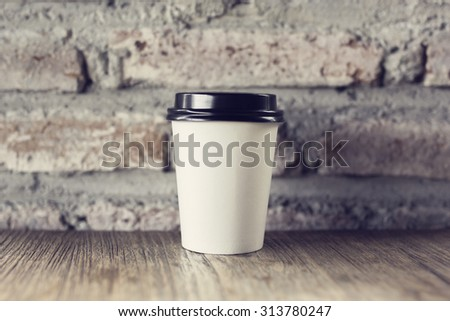 Coffee to go on a wooden table with vintage style wall - stock photo