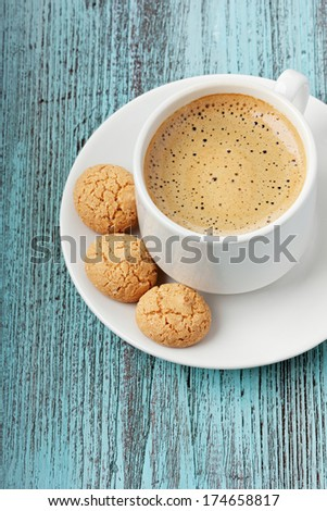 Coffee with biscuit cookies on a turquoise vintage surface - stock photo