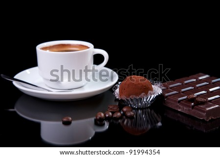 Coffee with chocolate - brigadier, on black with reflexion - stock photo