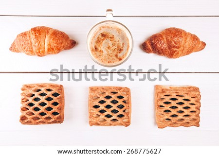 Coffee with croissants and baking lying on white wooden table - stock photo