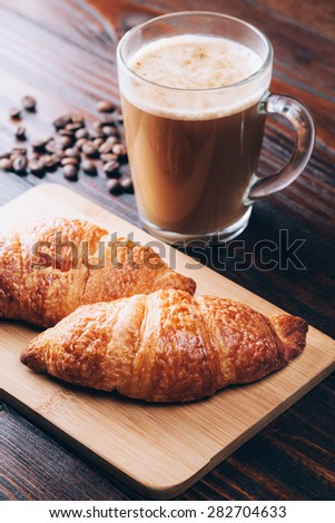 Coffee with croissants or baking lying on wooden table - stock photo
