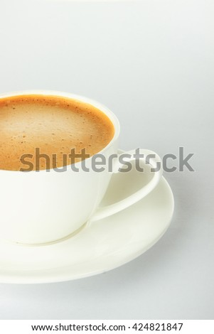 coffee with froth in white cup and saucer on a gray background - stock photo