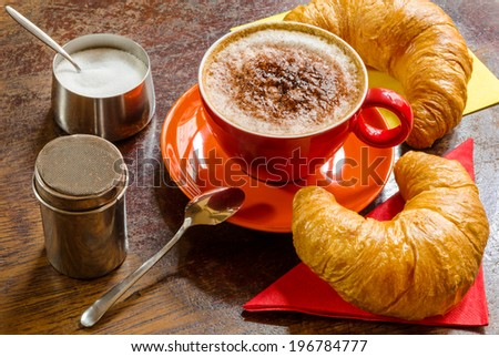 coffee with frothed milk, cocoa and croissants - stock photo