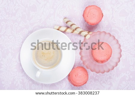 Coffee with milk, dessert, pink macaroons on the table, top view. Tasty breakfast - stock photo