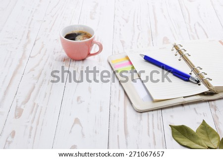 Coffee with notepad and pen on old white wooden table. - stock photo