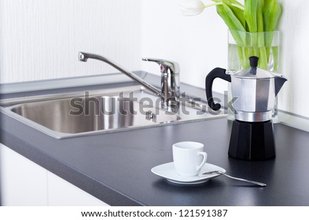 Coffeemaker and cup of coffee in kitchen interior - stock photo