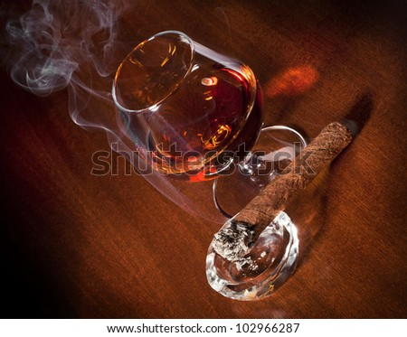 Cognac and Cigar with Smoke on dark background - stock photo