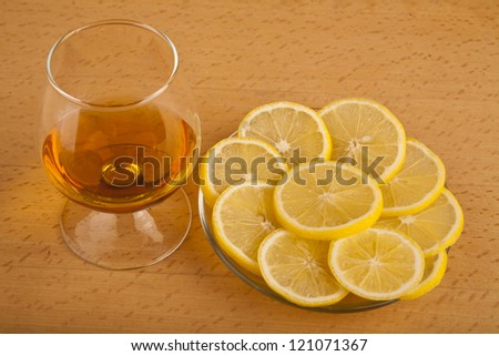 cognac and lemon on a wooden table - stock photo