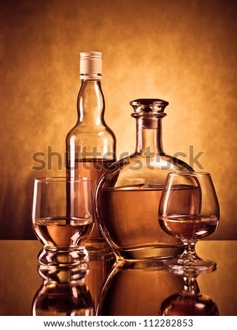 Cognac and whiskey bottles with filled glasses - stock photo