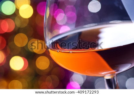 Cognac glass on a color iluminated background - stock photo