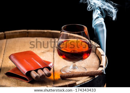 Cognac in a glass on wooden barrel - stock photo