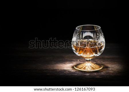Cognac in crystal glass on wooden background - stock photo