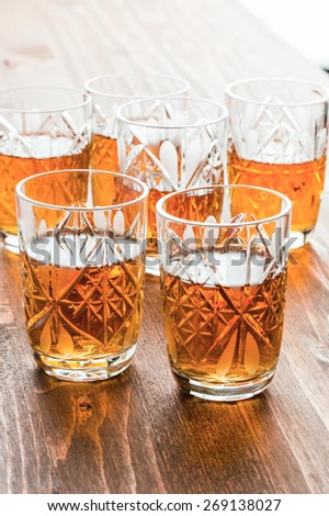 cognac in crystal wine glasses on a wooden table - stock photo