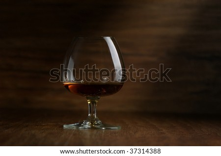 Cognac in the big glass on a dark background - stock photo
