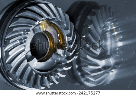 cogwheels with oil slicks mirrored in titanium - stock photo