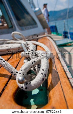coil of rope tied in a knot on a bollard - stock photo