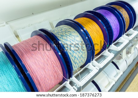 Coil with electric cable of different colors on a modern technological production   - stock photo