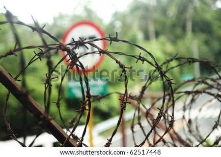 coiled barbed wire fence.narrow DOF - stock photo