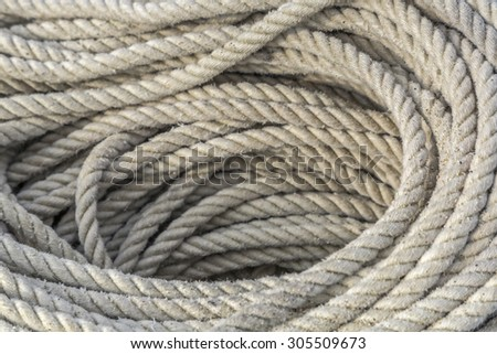 Coiled ship rope in an Italian port - stock photo