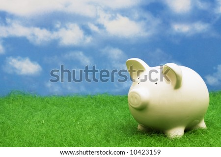 Coin bank sitting on grass with copy space - stock photo