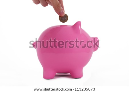 Coin holding by a human hand, fingers and pink piggy bank standing, isolated on white background. - stock photo