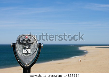 Coin operated binoculars for beach observation, blue sky and ocean, sandy beach - stock photo
