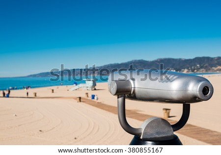 coin operated binoculars on a pier overlooking the beach - stock photo